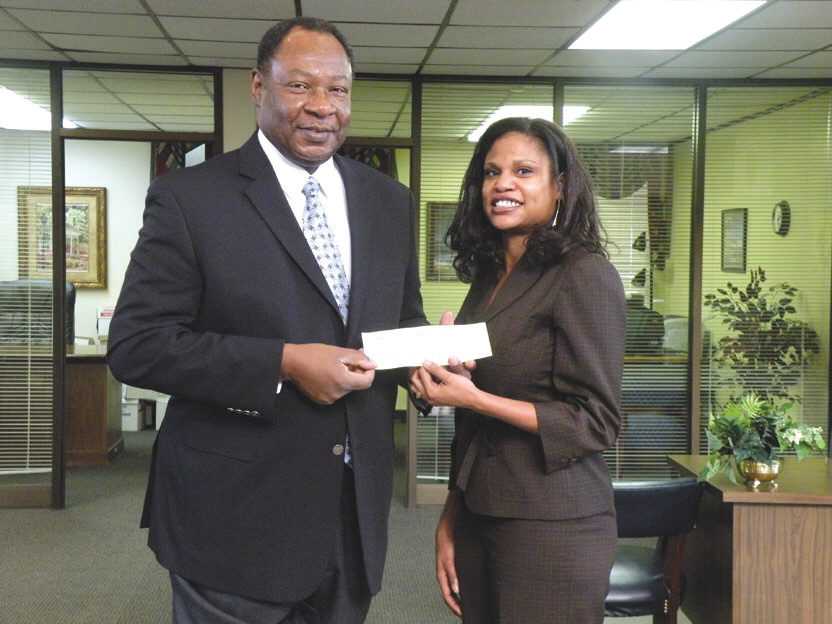 Vita Davis (r) receives a check from Robert E. James, President of Carver State Bank, after she was named Employee of the Year.