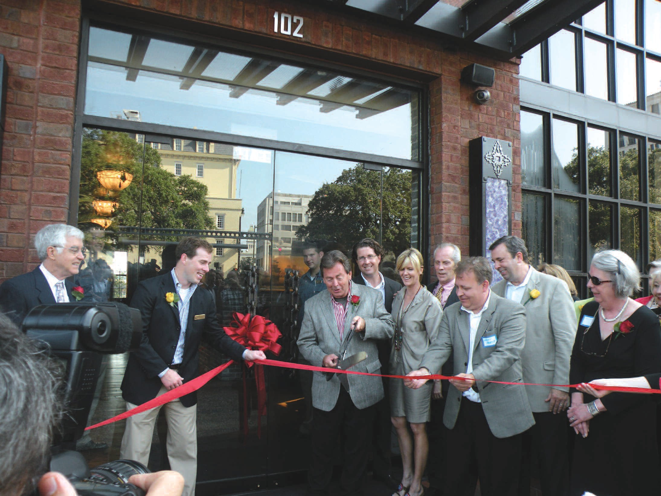Richard Kessler(with scissors) along with local dignitaries and hotel employees take part in the ribbon cutting ceremony