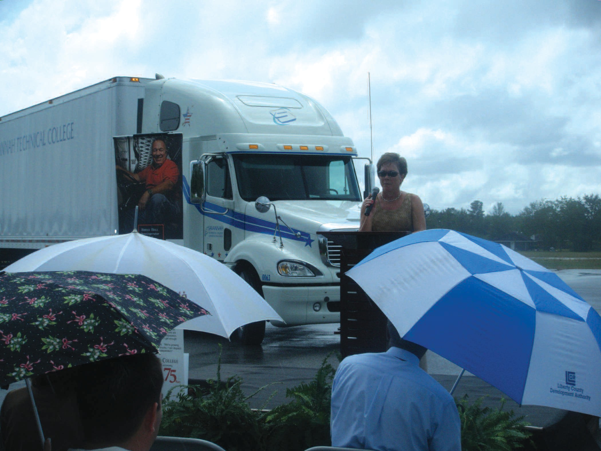 STC President Kathy Love addresses the crowd as the new STC truck is displayed in the background.