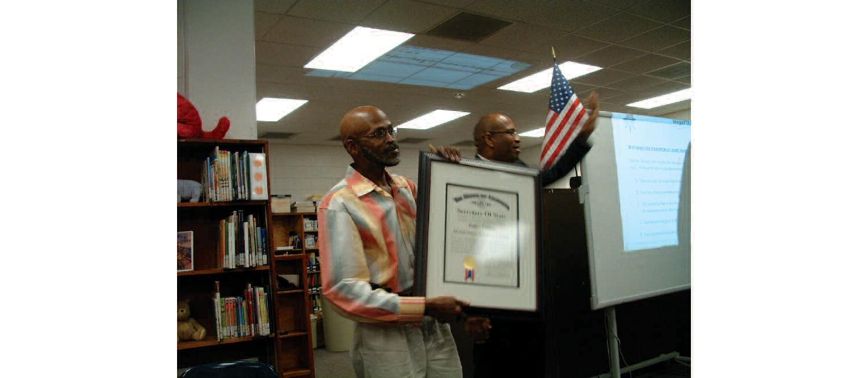 State Senator Lester Jackson presents James Putney with the Outstanding Georgia Citizen Award.