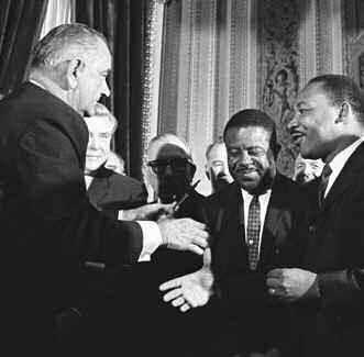 President Lyndon Johnson greets Rev. Ralph David Abernathy,and Rev. Martin Luther King, Jr. after siging the Voting Rights Bill in 1965