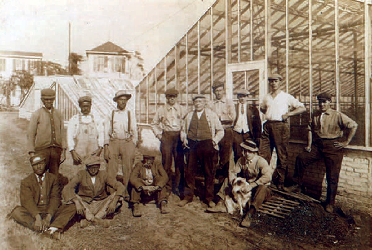 About 1910, Florist August Oelschig, center with cigar, flanked by his employees. Jonas, standing on the extreme left, was a resident of East Savannah and born into slavery. Sitting on the extreme left was Thomas, a flower deliveryman also from East Savannah. Courtesy George Oelschig.
