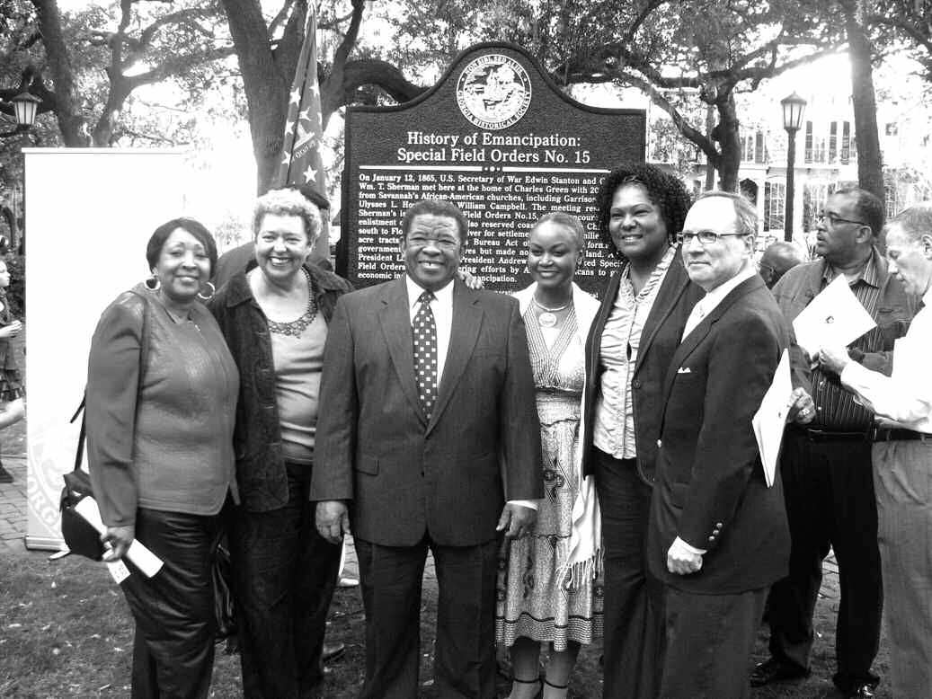 Dr. Charles Elmore, center, and others pose in front of the Special Field Order No. 15 marker