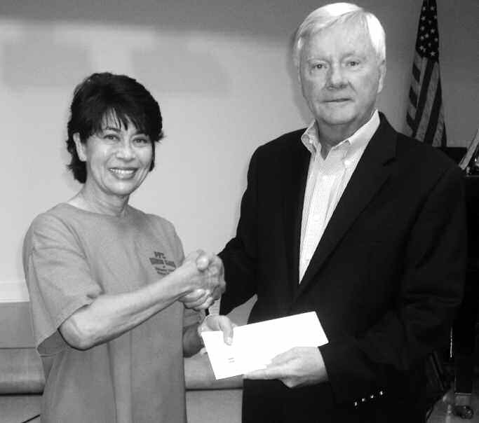 Patti Lott, local fitness instructor and personal trainer presents donation check to Union Mission CFO Skip Eloge.