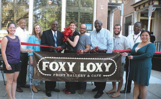 Community leaders, business owners and residents joined Jennifer Jenkins (c) during the ribbon cutting for Foxy Loxy Print Gallery and Cafe'