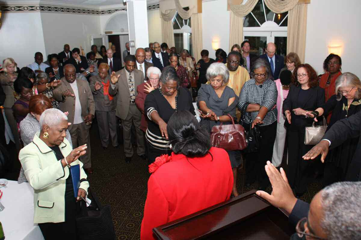Supporters pray for Edna Jackson as she kicks off her campaign