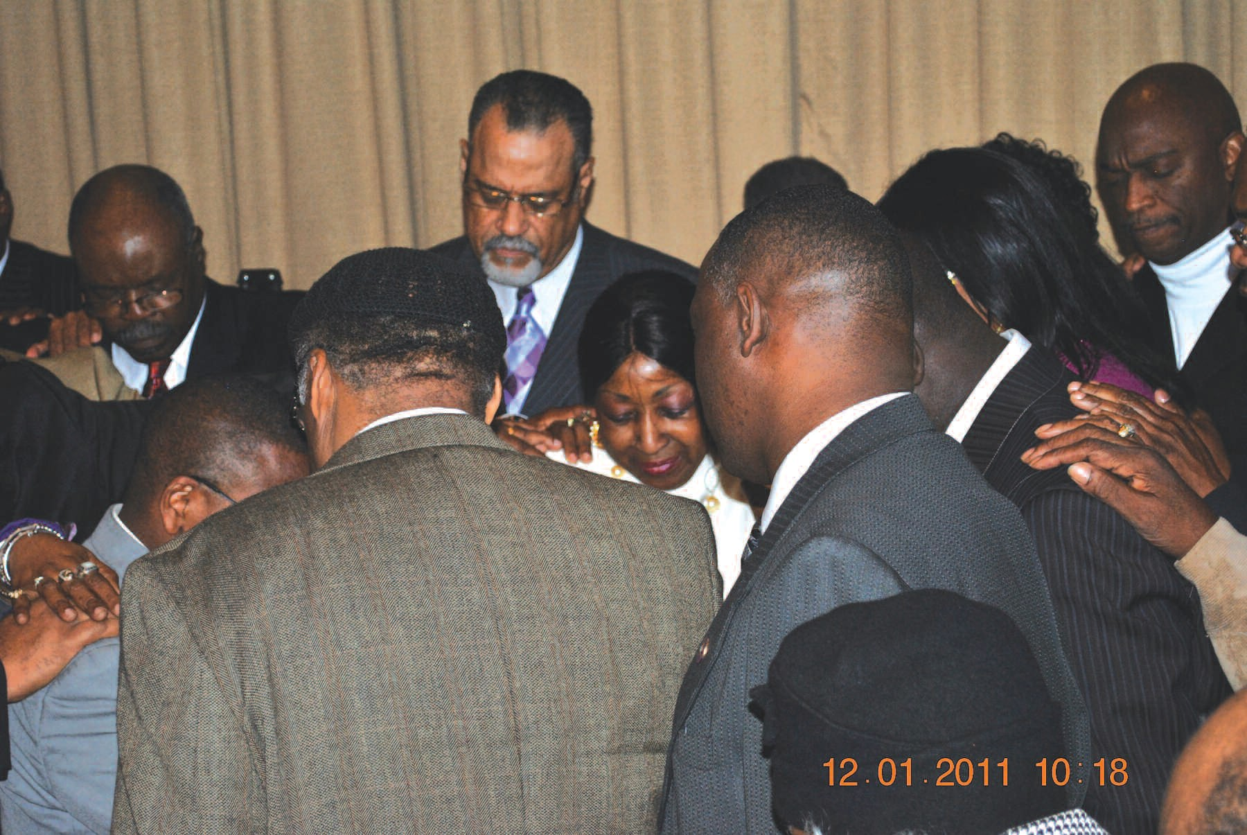 Jackson is surrounded by local ministers as they lift her in prayer