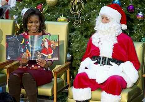 First lady Michelle Obama, accompanied by Santa Claus, reads