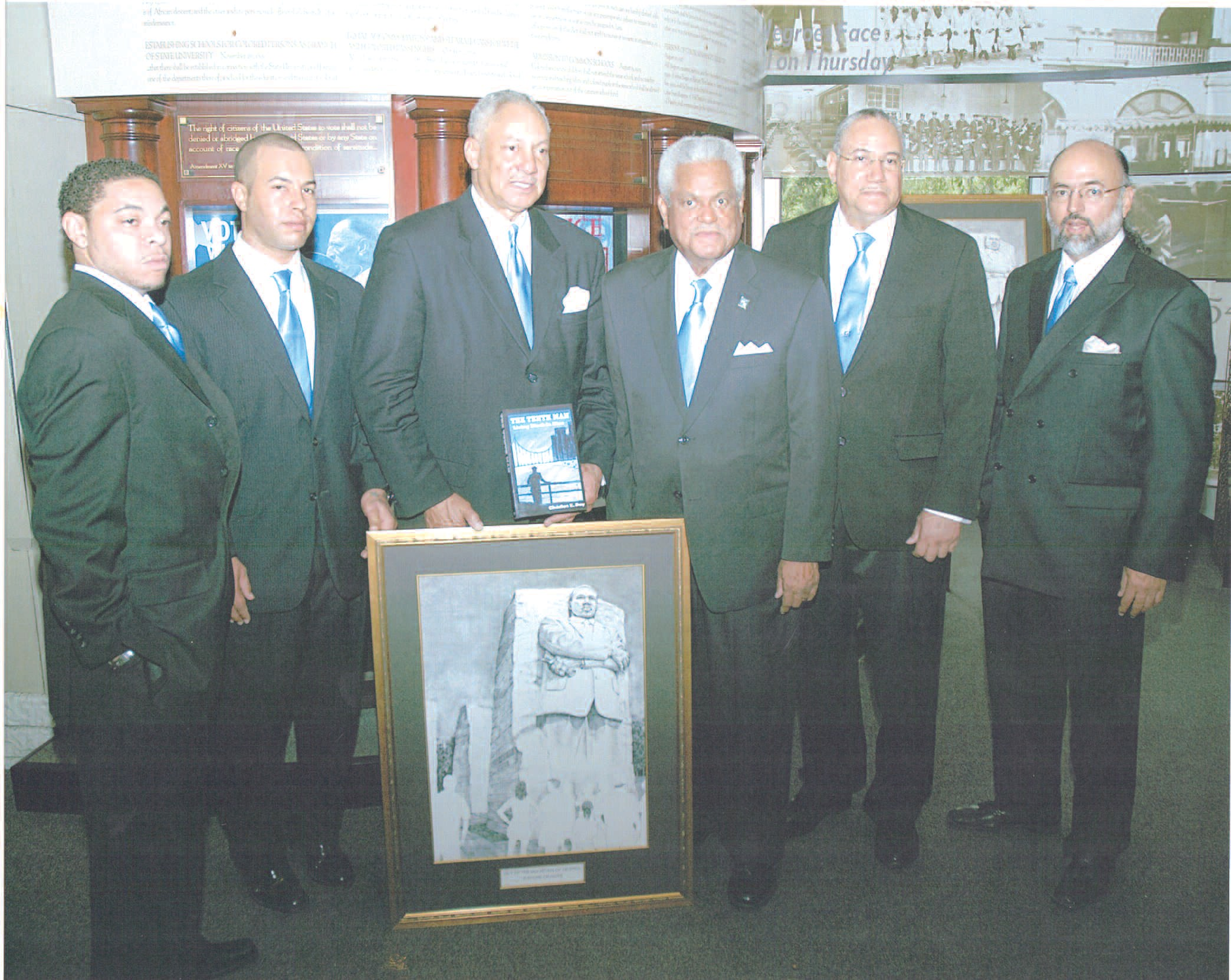Charles Day (third from left), son of William Day, along with brother Robert (second from right) and other family members present artwork to Billy Jamison, Chairman of the Museums Board of Directors