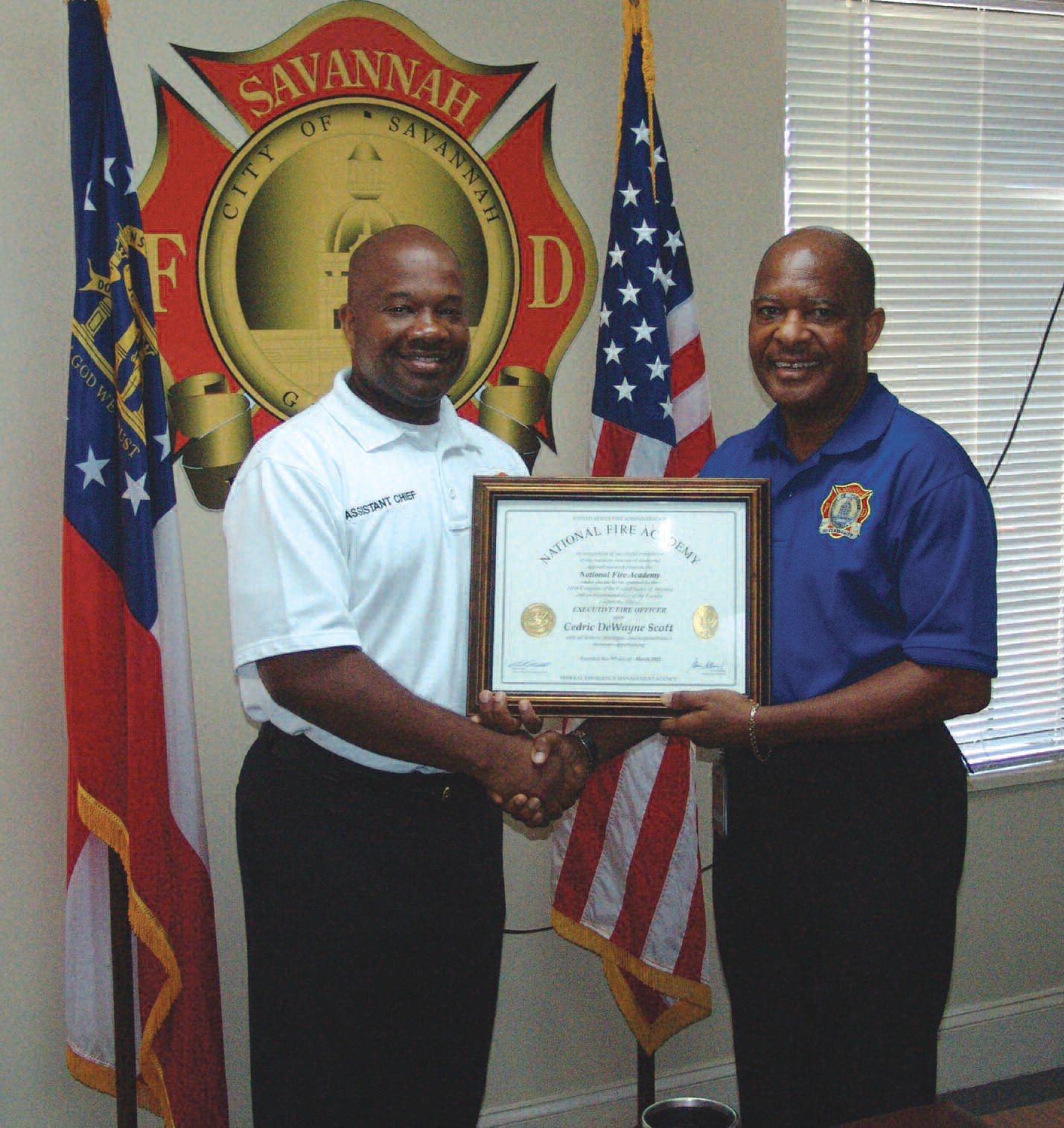 Savannah Fire Chief Charles G. Middleton (right) presents Assistant Fire Chief Cedric Scott with the Executive Fire Officer Program certificate