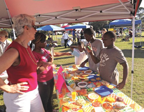 Jaden Gail, Troy Gail and Amyr Moore learn more about creating healthy meals Sunday at The Savannah Food Day Festival in Daffin Park from Virginia Bruce, Valeria Darby and other teachers from Johnson and Jenkins high schools.
