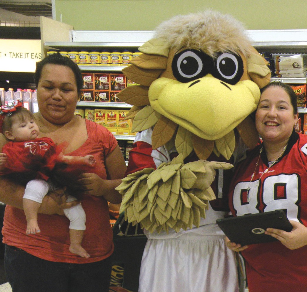 Winners of the home game tickets raffled off at Publix in the Twelve Oaks shopping center, pose with Freddie the Falcon