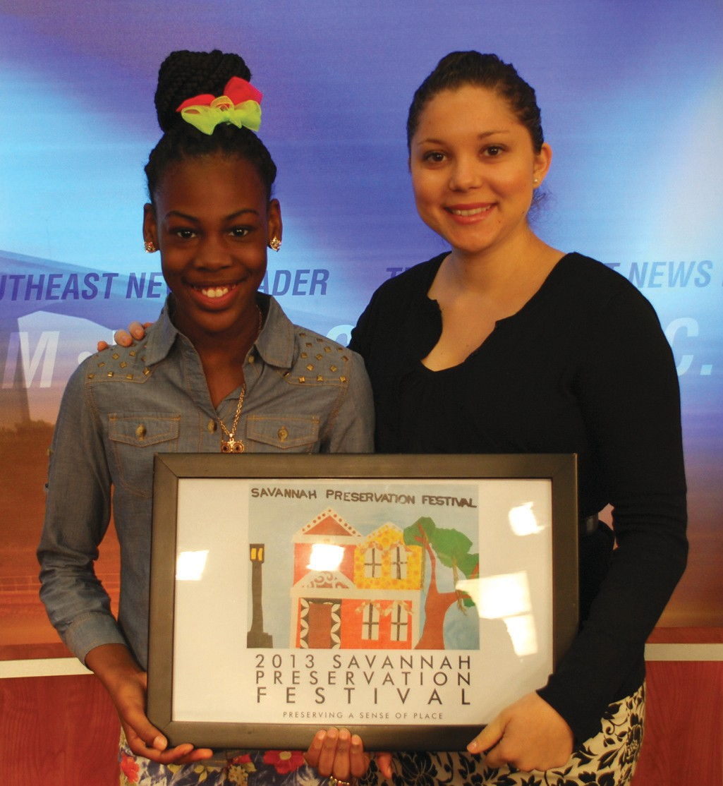 Historic Savannah Foundation's preservation and education coordinator Danielle Meunier, right, congratulates Gadsden Elementary School student Pe'lae Massey, left, for creating the design selected as the official 2013 Savannah Preservation Festival poster.