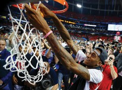 Injured Louisville Cardinals guard Kevin Ware cuts down the net as his team wins the NCAA National Cham-