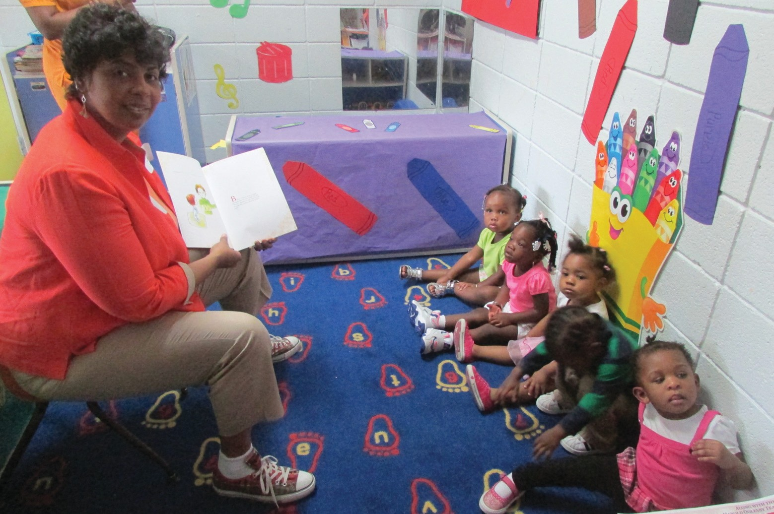 Author Gina Williams reading to children at the Book, Brownies, and Berries Day at Wesley Community Center.