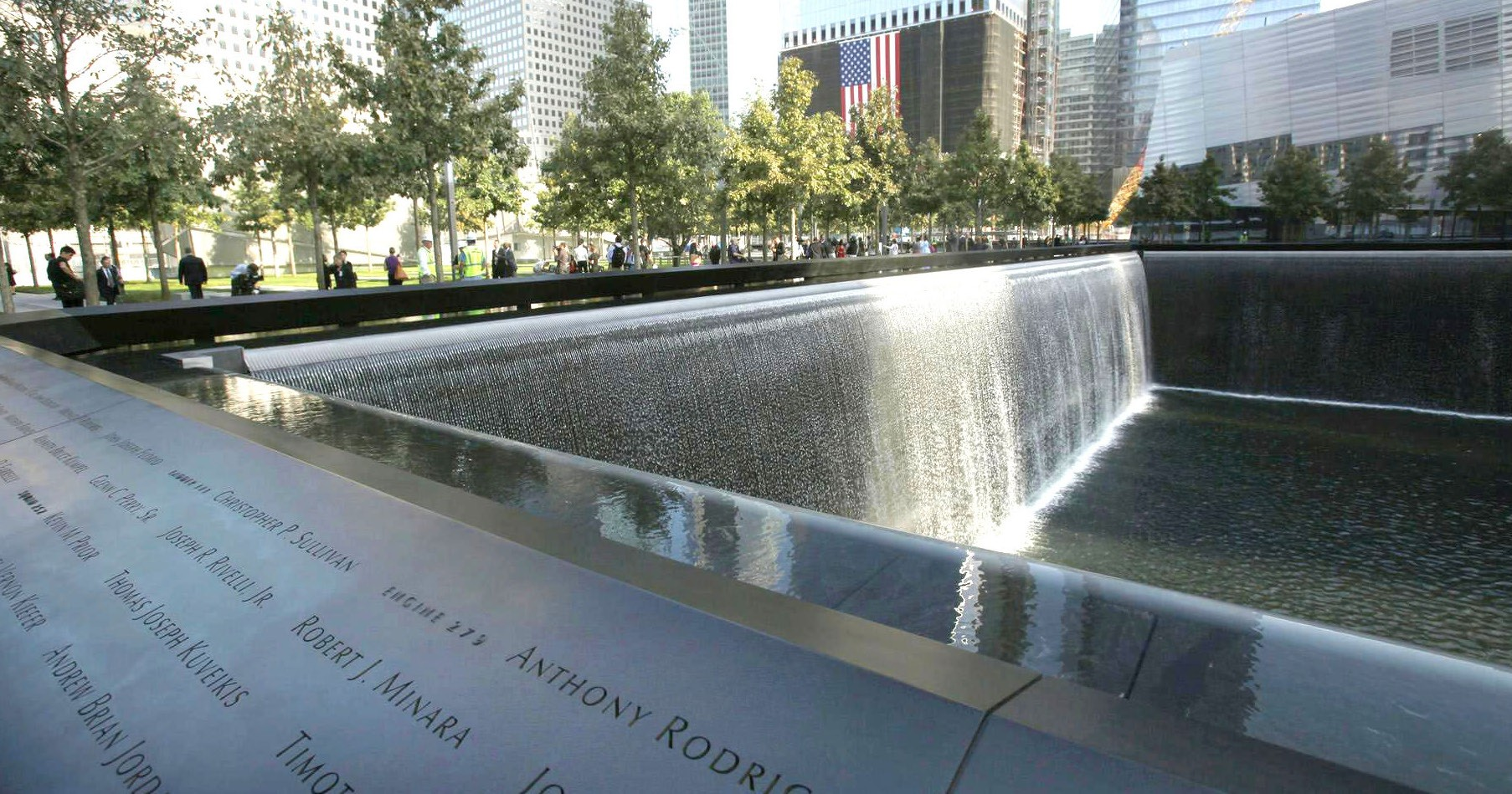 Visitors stroll the grounds near one of the pools at the 9/11 memorial plaza in the World Trade Center site in New York