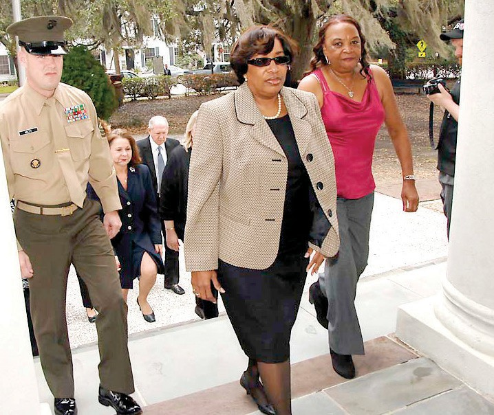 Jackie Hollins Lee ascends the steps of the Beaufort College Building, walking in the footsteps of her late father, James Hollins. She is escorted by Master Sergeant Christopher Allen Matt and accompanied by James Hollins' sister, Nancy Hampton.
