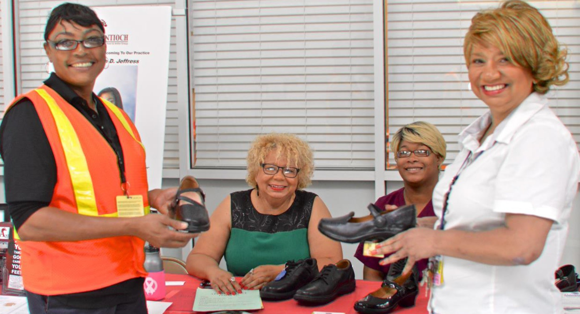 (Left) Antioch Foot & Ankle Group Team displaying comfortable work shoes and foot care products to below wing (orange vest) and above wing (white shirt) Delta Employees.