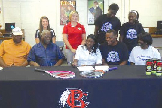 Vivian Moultrie, center, signs a letter of intent to play tennis for Albany State University. Also shown are: front from left, her uncle, Kenneth Moultrie, grandfather, William Moultrie, and parents, Keith and Natalie Moultrie; back from left, BCHS assistant tennis coach Laura Blair, BCHS head tennis coach Inga Cashon, Moultrie's brother, Keith Moultrie Jr., and her sister, Keyvona.