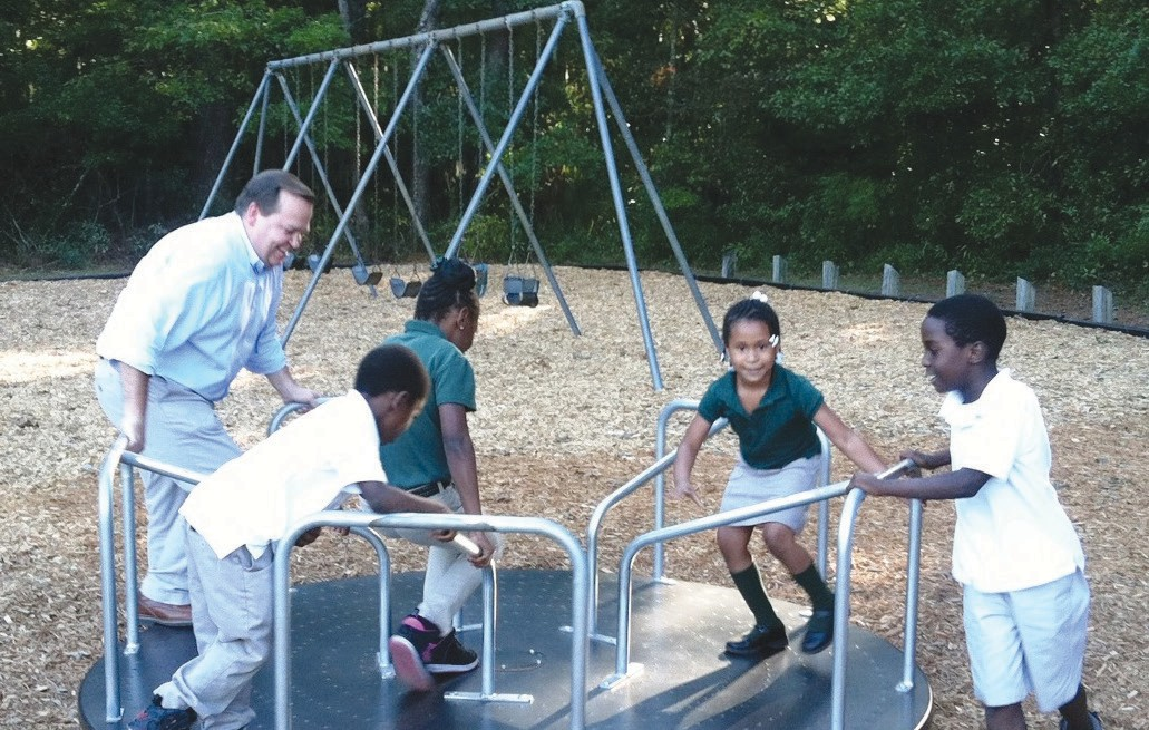 Savannah Alderman Tony Thomas and neighborhood children test ride some of the equipment at the new Crusader Park Neighborhood Center Playground, which opened Monday.