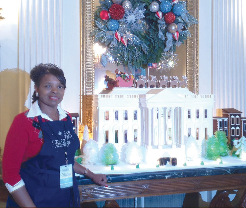 Sheri Saleem Scott with White House Gingerbread House in the State Dining Room