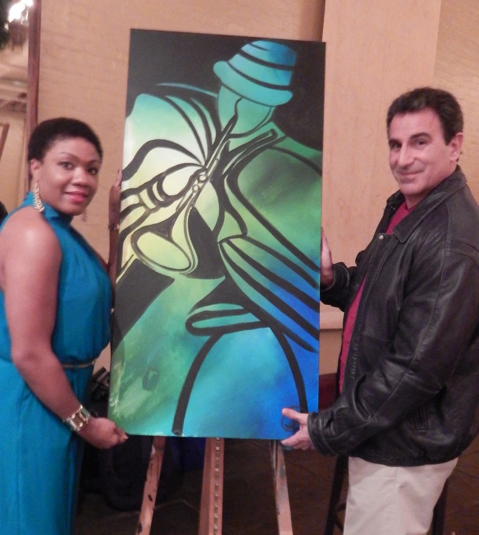Artist Sonja Robinson presents her real time live painting to concert attendee Peter Salas
