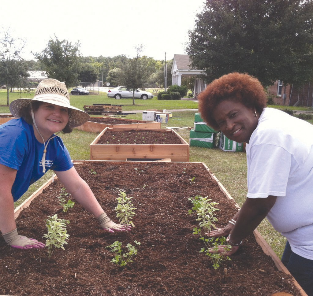 Metro Rotarian Whitney Shepherd and Greenbriar Children's Center Executive Director Gena Taylor plant a community garden last summer. The Rotary Club worked with Greenbriar children to build and plant more than a dozen raised bed gardens at the facility last summer.