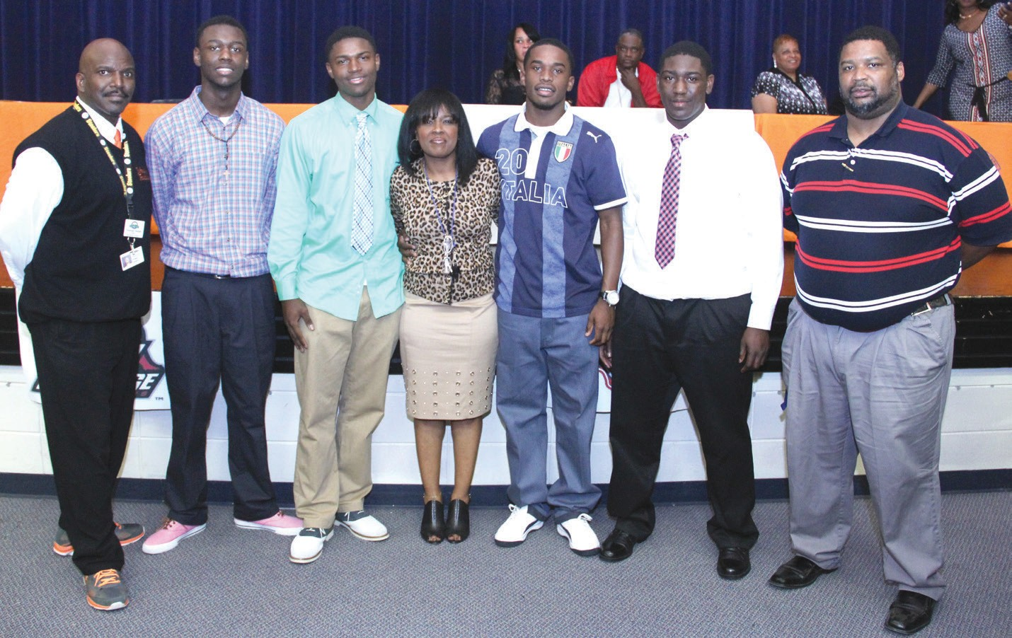 Players are shown with Principal Ms. Ball-Oliver and Football Coaches
