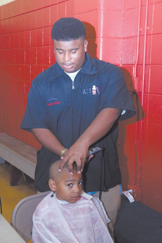 "Jowand ""Ali"" Brown of Holmes Barber Shop cuts Donald Washington Jr."