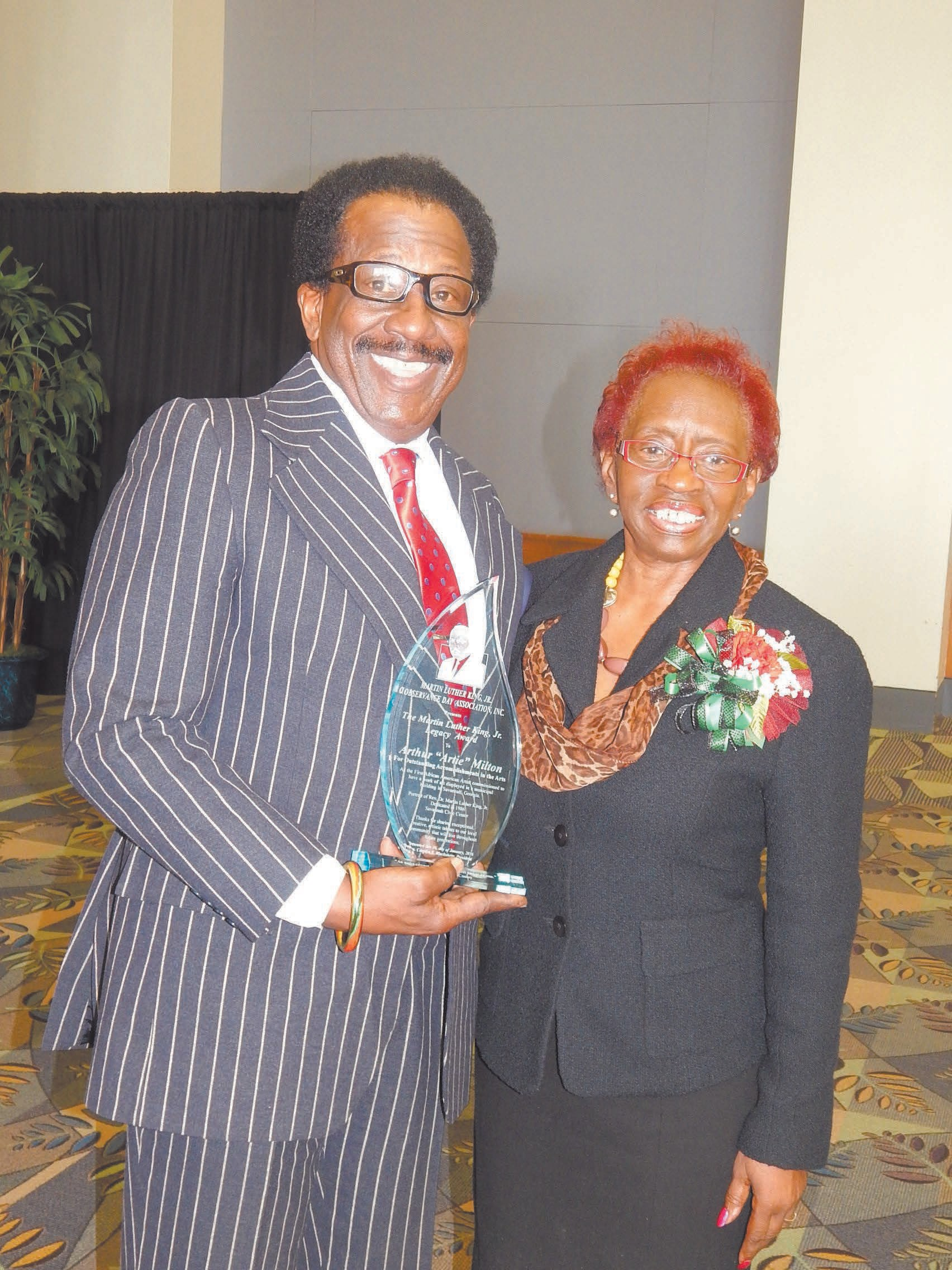 MLK Oberservance Day Committee President Carolyn Blackshear presents Artie Milton with the 2016 MLK Legacy Award for The Arts at the MLK Business and Community Unity Brunch held Saturday, January 16, 2016 at the International Trade and Convention Center. For more scenes of the 2016 MLK Observance Day Activities see page 9. For the listings of the upcoming