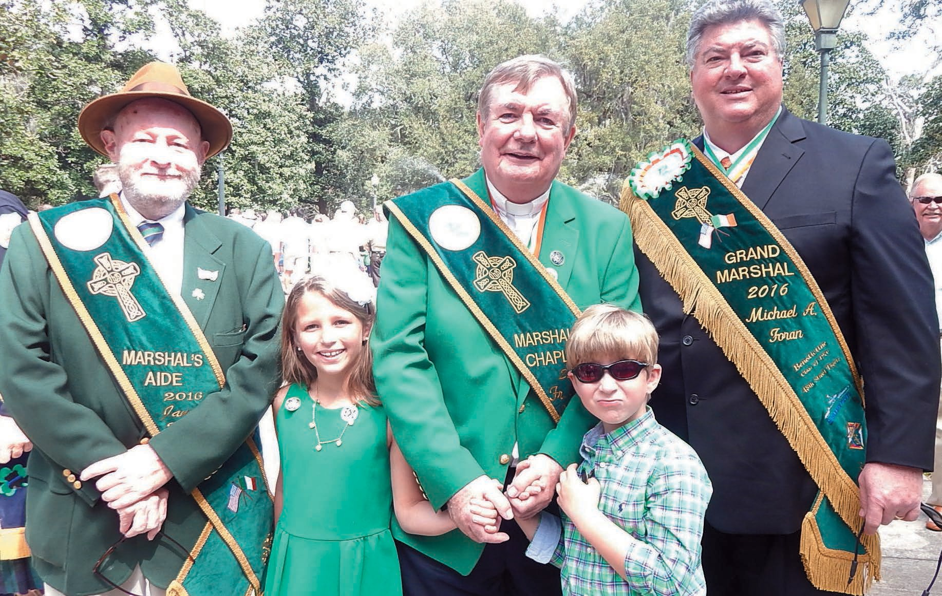 Jay Blackburn, Father Patrick O'Brian, and Grand Marshal Michael A. Foran shown with Addison and Matthew Gavin.