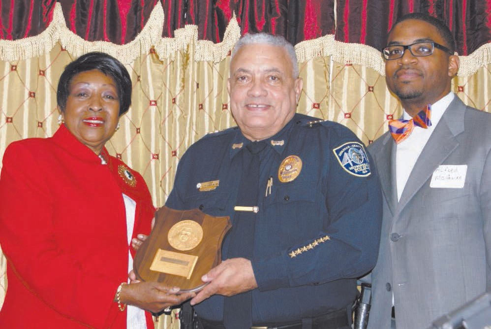 Edna Jackson, former City of Savannah Mayor, presents 2016 Whitney M Young, Jr. award to City of Savannah, Police Chief Joseph Lumpkin, Sr. - Savannah Chatham Metropolitan Police Department. Also shown, Master of Ceremonies, Alfred McGuire, Principal of Woodville Tompkins Technical and Career High School